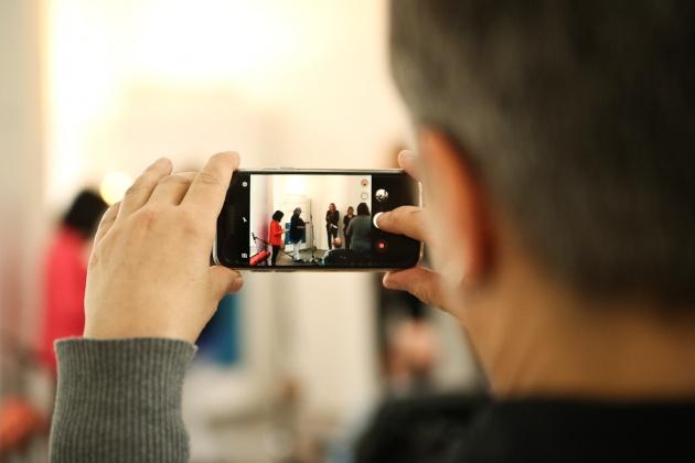 Ein Mensch filmt mit seinem Smartphone eine Pressekonferenz